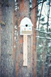 Ξύλινο birdhouse που συνδέεται με ένα δέντρο στο χειμερινό δάσος Στοκ Φωτογραφίες