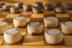 Ξύλινο checkerboard με τους ελεγκτές που χωρίζονται κατά διαστήματα στην επιτραπέζια κινηματογράφηση σε πρώτο πλάνο Στοκ Εικόνες