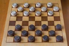 Ξύλινο checkerboard τους ελεγκτές που χωρίζονται κατά διαστήματα με στον πίνακα Στοκ Εικόνες