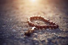 Ξύλινο rosary με έναν σταυρό βρίσκεται σε μια δύσκολη επιφάνεια στοκ φωτογραφίες με δικαίωμα ελεύθερης χρήσης