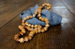 Ξύλινο rosary Ξύλινο rosary σε μια μπλε τσάντα σε ένα ξύλινο πάτωμα στοκ φωτογραφία με δικαίωμα ελεύθερης χρήσης