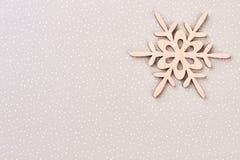 Ξύλινο snowflake στο υπόβαθρο χειμερινού εγγράφου Στοκ Φωτογραφίες