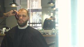 Ξύρισμα της γενειάδας του ατόμου στο κατάστημα κουρέων απόθεμα βίντεο