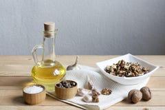 Ξύλα καρυδιάς σε ένα λευκό κύπελλο, ένα σκόρδο, ένα άλας πιπεριών και ένα έλαιο σε ένα ξύλινο υπόβαθρο, έναν ξύλινο πίνακα και μι Στοκ φωτογραφίες με δικαίωμα ελεύθερης χρήσης