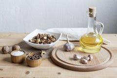 Ξύλα καρυδιάς σε ένα λευκό κύπελλο, ένα σκόρδο, ένα άλας πιπεριών και ένα έλαιο σε ένα ξύλινο υπόβαθρο, έναν ξύλινο πίνακα και μι Στοκ εικόνα με δικαίωμα ελεύθερης χρήσης