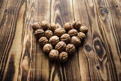 Ξύλα καρυδιάς στην καρδιά στο ξύλινο υπόβαθρο Στοκ Εικόνες