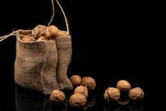 Ξύλα καρυδιάς στην τσάντα σε ένα μαύρο υπόβαθρο Στοκ Φωτογραφίες