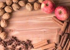 Ξύλα καρυδιάς υποβάθρου, αστέρια γλυκάνισου, sinnamons και δύο μήλα Στοκ εικόνα με δικαίωμα ελεύθερης χρήσης