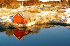 Ξύλινα εξοχικό σπίτι και rorbu πέρα από τον κόλπο Στοκ Εικόνες