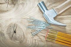 Ξύλινα καρφιά κατασκευής μετρητών σφυριών νυχιών στην ξύλινη κορυφή VI πινάκων Στοκ Εικόνες
