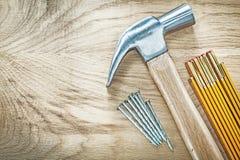 Ξύλινα καρφιά κατασκευής μετρητών σφυριών νυχιών στο ξύλινο buildi πινάκων Στοκ εικόνα με δικαίωμα ελεύθερης χρήσης