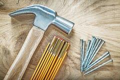Ξύλινα καρφιά μετάλλων μετρητών σφυριών νυχιών στην ξύλινη οικοδόμηση πινάκων συμπυκνωμένη Στοκ Εικόνες