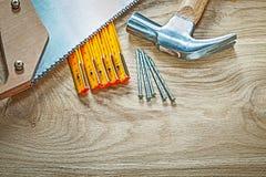 Ξύλινα καρφιά μετρητών σφυριών νυχιών handsaw στο ξύλινο constructio πινάκων Στοκ Εικόνα