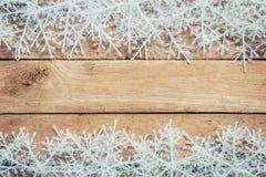 Ξύλινα καφετιά υπόβαθρο και snowflakes Χριστουγέννων με το διάστημα Στοκ Φωτογραφία