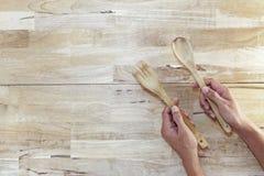 ξύλινα κουτάλι και δίκρανο λαβής χεριών στο ξύλινο υπόβαθρο Στοκ Φωτογραφίες
