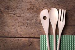 Ξύλινα μαχαιροπήρουνα κουζινών στο ξύλινο υπόβαθρο Στοκ Φωτογραφίες