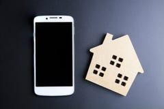 Ξύλινα παιχνίδι και Smartphone σπιτιών στο μαύρο υπόβαθρο με το αντίγραφο SP Στοκ φωτογραφίες με δικαίωμα ελεύθερης χρήσης
