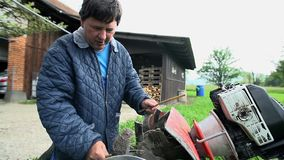 Ξύλινα ραβδιά χρήσεων της Farmer για να καθαρίσει τα βρώμικα μέρη του αρότρου απόθεμα βίντεο