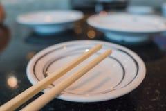 Ξύλινα Chopsticks σε ένα άσπρο πιάτο Στοκ εικόνα με δικαίωμα ελεύθερης χρήσης