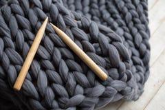 Ξύλινες πλέκοντας βελόνες στο υπόβαθρο του γκρίζου μερινός μαλλιού Στοκ Εικόνες