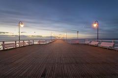 Ξύλινη αποβάθρα από τη θάλασσα αναμμένη από τους μοντέρνους λαμπτήρες τη νύχτα Στοκ Εικόνα
