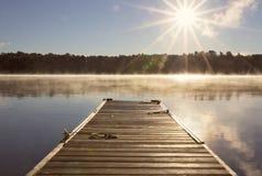 Ξύλινη αποβάθρα πέρα από μια ήρεμη λίμνη με την ομίχλη στα ξημερώματα Στοκ Εικόνες
