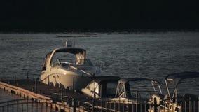 Ξύλινη αποβάθρα στο ηλιοβασίλεμα βραδιού Βάρκα μηχανών που στέκεται κοντά στην ακτή Ήρεμος χρόνος στη φύση, κύματα στον ποταμό απόθεμα βίντεο