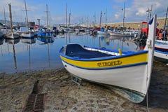 Ξύλινη βάρκα Αγίου Tropez με τη σαφή αντανάκλαση και το τουβλότοιχο νερού που οδηγεί στο φάρο στοκ εικόνες με δικαίωμα ελεύθερης χρήσης