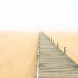 Ξύλινη γέφυρα για πεζούς σε μια ομιχλώδη ανασκόπηση παραλιών άμμου. Πορτογαλία. στοκ φωτογραφία με δικαίωμα ελεύθερης χρήσης