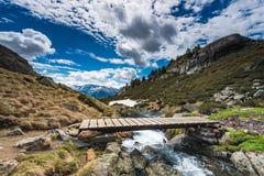 Ξύλινη γέφυρα πέρα από το άγριο ρεύμα βουνών Στοκ φωτογραφία με δικαίωμα ελεύθερης χρήσης