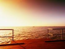 Ξύλινη γέφυρα στη θάλασσα στο ηλιοβασίλεμα Απάνεμος καιρός, ειρηνική σιωπηλή ημέρα στον κόλπο Στοκ Εικόνες