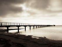 Ξύλινη γέφυρα στη θάλασσα στο ηλιοβασίλεμα Απάνεμος καιρός, ειρηνική σιωπηλή ημέρα στον κόλπο Στοκ Φωτογραφία
