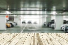 Ξύλινη επιτραπέζια κορυφή θολωμένα στα χώρος στάθμευσης υπόβαθρα Στοκ Εικόνες