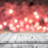 Ξύλινη επιτραπέζια κορυφή με το ανοικτό κόκκινο αφηρημένο υπόβαθρο bokeh Στοκ Φωτογραφίες