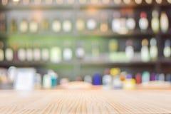 Ξύλινη επιτραπέζια κορυφή με το θολωμένο υπόβαθρο επίδειξης μπουκαλιών ποτού κρασιού Στοκ φωτογραφία με δικαίωμα ελεύθερης χρήσης