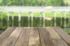 Ξύλινη επιτραπέζια κορυφή στα πράσινα θολωμένα φύση υπόβαθρα Στοκ φωτογραφία με δικαίωμα ελεύθερης χρήσης