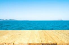 Ξύλινη επιτραπέζια κορυφή στην μπλε θάλασσα & τον ουρανό Στοκ φωτογραφία με δικαίωμα ελεύθερης χρήσης
