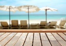 Ξύλινη επιτραπέζια κορυφή στη θολωμένη μπλε θάλασσα και το άσπρο υπόβαθρο παραλιών άμμου στοκ φωτογραφία με δικαίωμα ελεύθερης χρήσης
