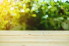 Ξύλινη επιτραπέζια κορυφή στο σαλιασμένο πράσινο φυσικό υπόβαθρο Στοκ εικόνες με δικαίωμα ελεύθερης χρήσης