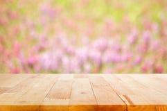 Ξύλινη επιτραπέζια κορυφή στο υπόβαθρο κήπων λουλουδιών θαμπάδων Στοκ Φωτογραφία