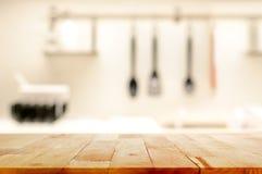 Ξύλινη επιτραπέζια κορυφή (ως νησί κουζινών) στο υπόβαθρο κουζινών θαμπάδων Στοκ Εικόνα
