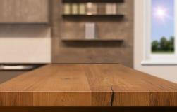 Ξύλινη επιτραπέζια κορυφή ως νησί κουζινών στο υπόβαθρο κουζινών θαμπάδων - μπορεί να χρησιμοποιηθεί για την επίδειξη ή το montag στοκ φωτογραφία με δικαίωμα ελεύθερης χρήσης