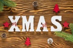 Ξύλινη διακόσμηση Χριστουγέννων στο καφετί και κόκκινο χρώμα με το χριστουγεννιάτικο δέντρο, Στοκ Εικόνα
