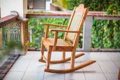 Ξύλινη λικνίζοντας καρέκλα στο πεζούλι ενός εξωτικού Στοκ εικόνα με δικαίωμα ελεύθερης χρήσης