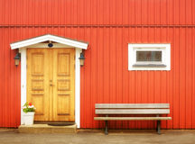 Ξύλινη κίτρινη πόρτα στο πορτοκαλί κτήριο Στοκ εικόνα με δικαίωμα ελεύθερης χρήσης