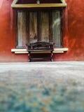 Ξύλινη καρέκλα και κόκκινο παράθυρο τοίχων πετρών ξύλινο στοκ εικόνα