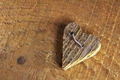 Ξύλινη καρδιά που καρφώνεται στο ξύλινο υπόβαθρο Στοκ Εικόνες