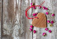 Ξύλινη καρδιά με την κόκκινη κορδέλλα και μικρά ξηρά μπουμπούκια τριαντάφυλλου σε ένα woode Στοκ Εικόνες