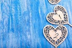 Ξύλινη καρδιά που χαράζεται σε ένα μπλε ξύλινο υπόβαθρο Στοκ Φωτογραφίες