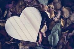 Ξύλινη καρδιά στα ξηρά ροδαλά πέταλα Στοκ Φωτογραφία